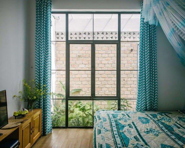 Phòng ngủ đẹp và yên bình với cửa kính lớn nhìn ra khu vườn sau nhà.