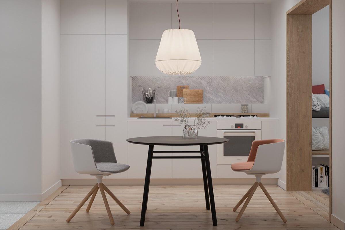 white kitchen tiny table chairs kitchen Hô biến căn hộ dưới 50m2 thành không gian rộng rãi và cá tính qpdesign
